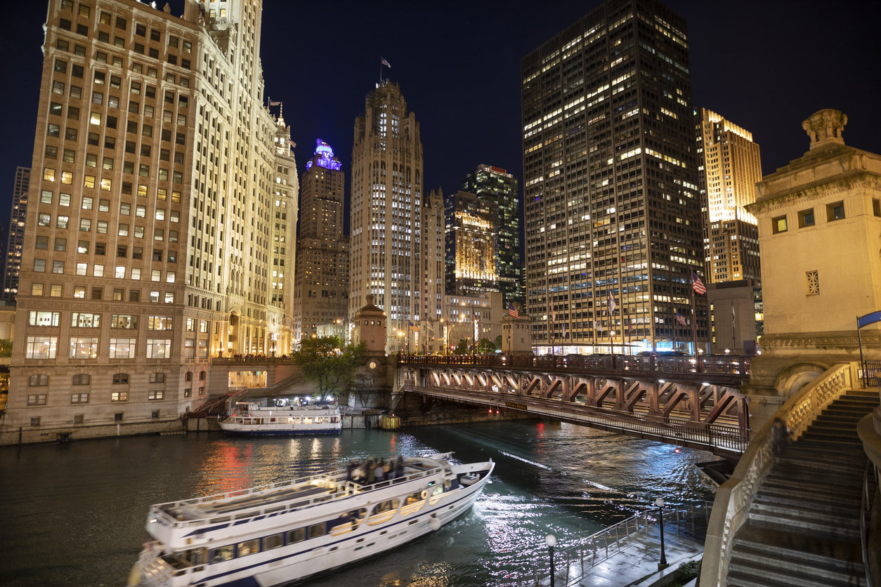 Ferry boat passes under the DuSable Bridge over the Chicago River in downtown Chicago Illinois USA during a summer night